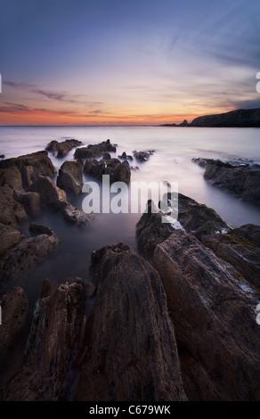 Rocky seashore at dusk near Thurlestone, Devon - Stock Photo