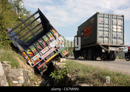 Decorated Nepali truck in a drainage ditch after accident on the highway - Stock Photo