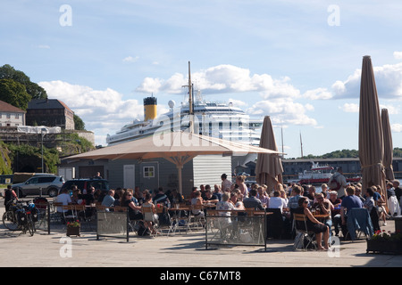 Picture shows a cruise liner moored at Oslo Harbour, whilst people sit outside in the sun, Norway. Photo:Jeff Gilbert - Stock Photo