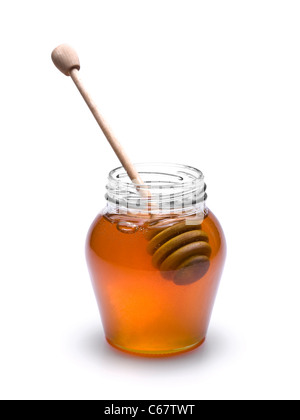 Jar of honey with a wooden drizzler inside. Isolated on white background. - Stock Photo
