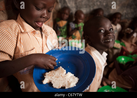 Young school children eat a meal of posho, or ugali, at a school in Amuria, Uganda, East Africa. - Stock Photo