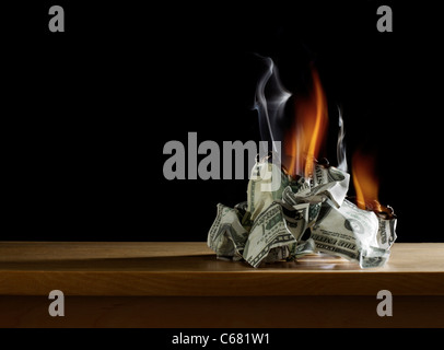 Pile of Money Burning on Table - Stock Photo