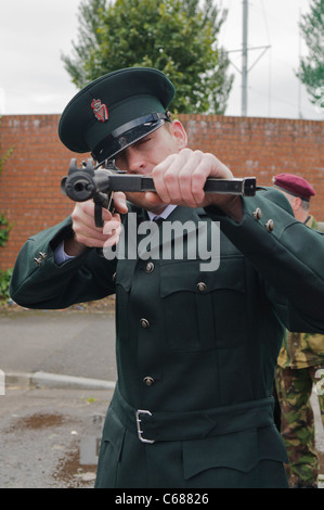 Man dressed in RUC police uniform, pointing a Sterling Machine Gun - Stock Photo