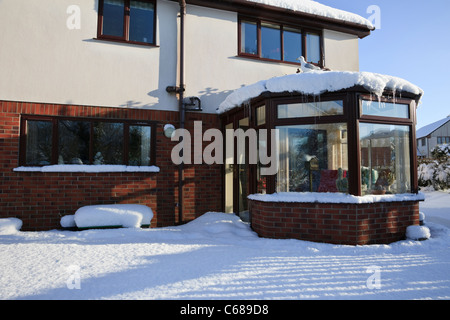 House with conservatory from back garden covered in snow in winter 2010. UK - Stock Photo