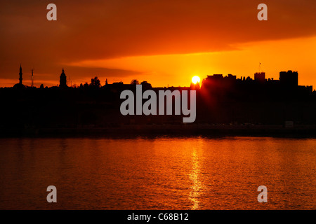 Sunset at the seaside walls, at Sahtouri coast,  of the Medieval town of Rhodes (World Heritage site by UNESCO), - Stock Photo