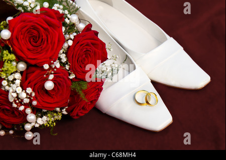 wedding symbol concept with white bridal dancing shoes a red roses bridal bouquet and two entwined golden wedding - Stock Photo