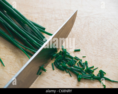 Schnittlauch wird auf einem Schneidbrett geschnitten | Chives is cutting on a cutting board - Stock Photo