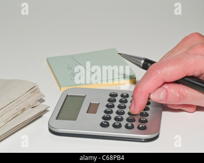 a hand with a pen above a pocket calculator, besides is a yellow paper block with data and a newspaper - Stock Photo