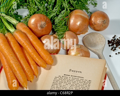 an old German cookbook side by side with carrots, onions and peppercorns and a wooden spoon - Stock Photo
