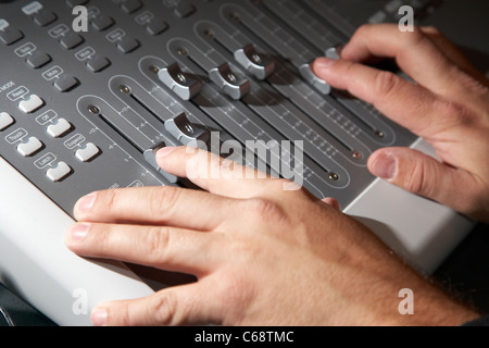 sound engineers hands working on a mixing desk in a recording studio - Stock Photo