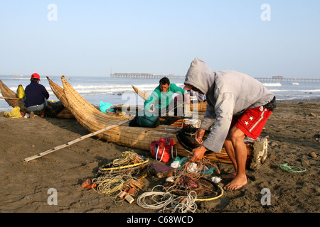 Caballitos de Totora reed boat fishermen prepare their nets for another days fishing. Pimentel, Lambayeque, Peru, - Stock Photo