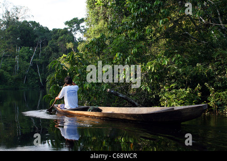 Jungle fisherman paddles upriver on the Rio Samiria in the Amazon rain forest, Loreto, Peru, South America - Stock Photo