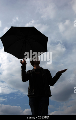 Man standing against a cloudy sky, hand out checking for rain, holding an umbrella. - Stock Photo