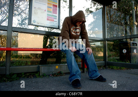 Young man wearing a hoodie sitting in bus shelter - Stock Photo