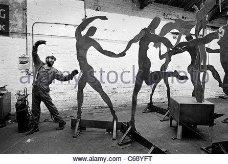 Welder imitates dancing sculptures in his Birmingham workshop.  He adopts the pose of the dancing figures. - Stock Photo