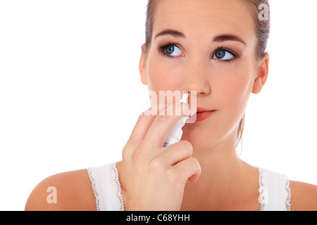 Attractive young woman using nasal spray. All on white background. - Stock Photo