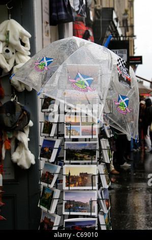 See through umbrella protecting stock of picture postcards on a rack during rain. Edinburgh Scotland - Stock Photo