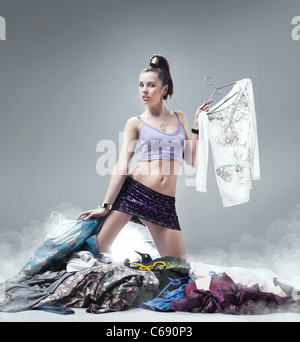 Portrait of pretty woman choosing new clothes and looking at camera - Stock Photo