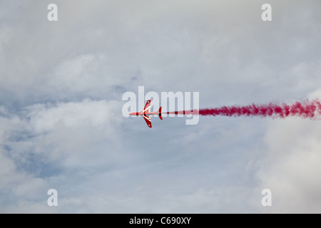 Red Arrow flies against cloudy sky with red smoke - Stock Photo