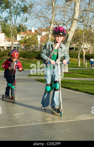 Wearing jacket Young girl 6-7 year old and pre-K Hispanic boy 4-5 years old on scooters at park. MR © Myrleen Pearson - Stock Photo