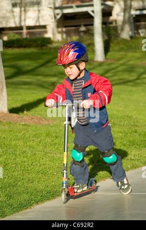 Wearing jacket Pre-K Hispanic boy riding on scooter at park. MR © Myrleen Pearson - Stock Photo
