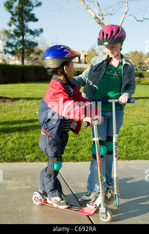 Wearing jacket Young girl and pre-K Hispanic boy on scooters at park child helping another  MR © Myrleen Pearson - Stock Photo