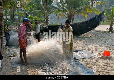 Families sorting fishing nets on Marari Beach Kerala South India - Stock Photo