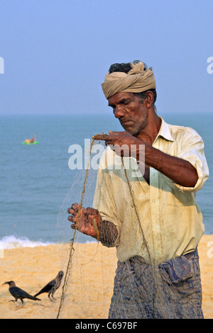 Portrait fisherman sorting fishing nets on Marari Beach Kerala South India - Stock Photo