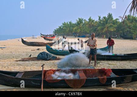 Fishermen sorting fishing nets on Marari Beach Kerala South India - Stock Photo