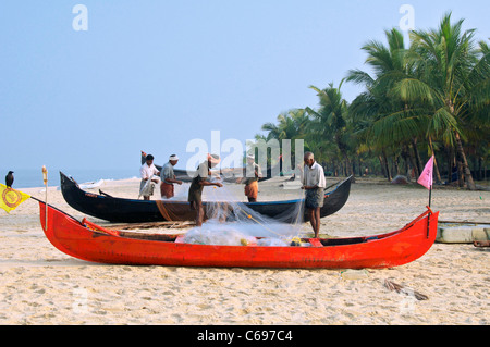 Fishermen sorting fishing nets on Marari Beach Kerala South India - Stock Photo