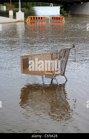 abandoned safeway shopping trolley in the red river in flood at the forks Winnipeg Manitoba Canada - Stock Photo