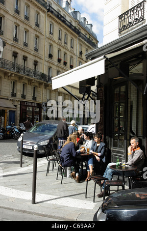 Tourists enjoying a relaxing drink in the sunshine outside a quiet pavement cafe in Paris, France - Stock Photo