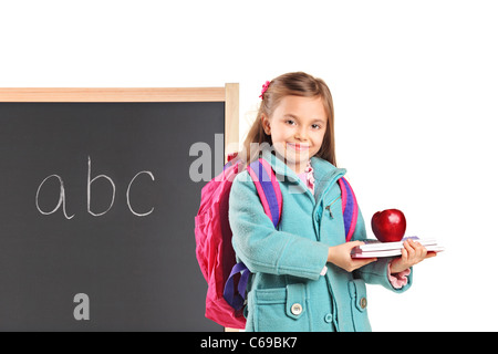 4180f14c9d48 A school girl with backpack holding notebooks and an apple - Stock Photo