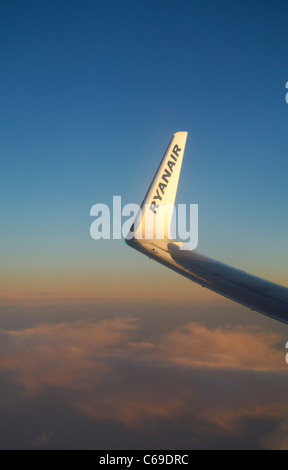 Wing tip of Ryanair Boeing 737-800 airliner plane at sunset over Atlantic Ocean - Stock Photo