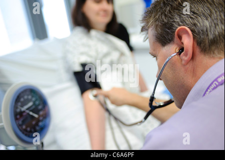 doctor checking blood pressure of patient and using stethoscope hospital bed patient and doctor not identifiable - Stock Photo