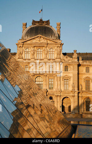 PARIS,FRANCE - JUNE 16: The large pyramid in Louvre and facade of Pavillon Sully in sunset light - Stock Photo