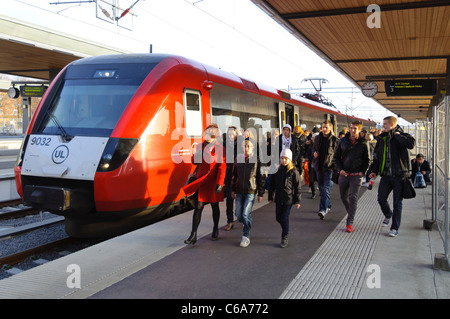 Fast higher-speed commuter train at a station with crowds of passengers on the platform - Stock Photo