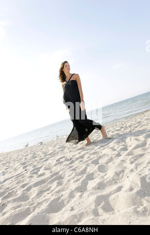 Young woman, 20+, standing in a long dress on the beach, lifestyle, sensuality, space, lightness, Niendorf at the - Stock Photo