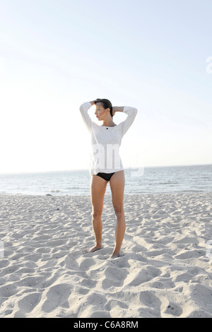Young woman, 20+, standing on a sandy beach, lifestyle, sensuality, Niendorf at the Baltic Sea, Schleswig-Holstein, Germany