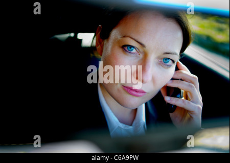 A close up of a young businesswoman on mobile phone in a car, UK - Stock Photo
