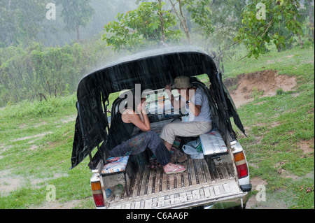 Two women take shelter from heavy rain in the back of a 4x4 vehicle Thailand Asia - Stock Photo