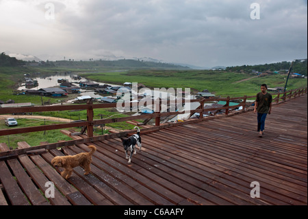 A local man with two dogs crossing The Mon wooden bridge in Sangkhlaburi, Kanchanaburi province, Thailand - Stock Photo