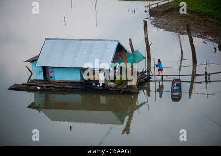 House chores on board a wooden floating family home along the banks of Sangkhlaburi Thailand - Stock Photo