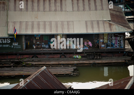 A family relax in their floating house Sangkhlaburi Thailand - Stock Photo