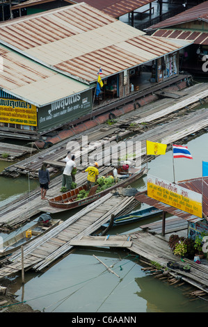 Unloading bananas at a floating village on the river Songaria, in Sangkhlaburi, Kanchanaburi province Thailand - Stock Photo