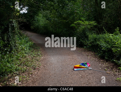 A broken umbrella left on a path in the Langdon Hills Country Park in Essex - Stock Photo