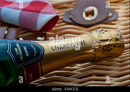 Close view on Champagne bottle on wicker picnic hamper at luxury alfresco summer event picnic situation - Stock Photo