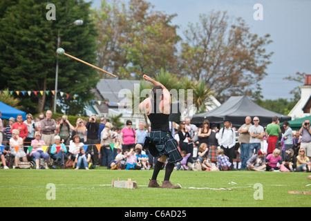 Competitor throwing a Hammer during a competition in the Scottish Standing Style at Brodick Highland Games, Isle - Stock Photo