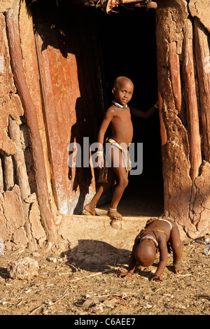 Himba children in front of house in village near Opuwo, Namibia - Stock Photo