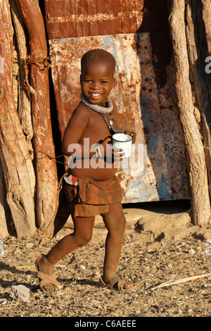 Young Himba girl in traditional dress, village near Opuwo, Namibia - Stock Photo